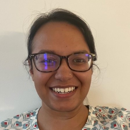 HSDC staff member Bunny Grewal smiles for camera. Bunny is feminine-presenting, with olive skin, dark hair, and glasses.